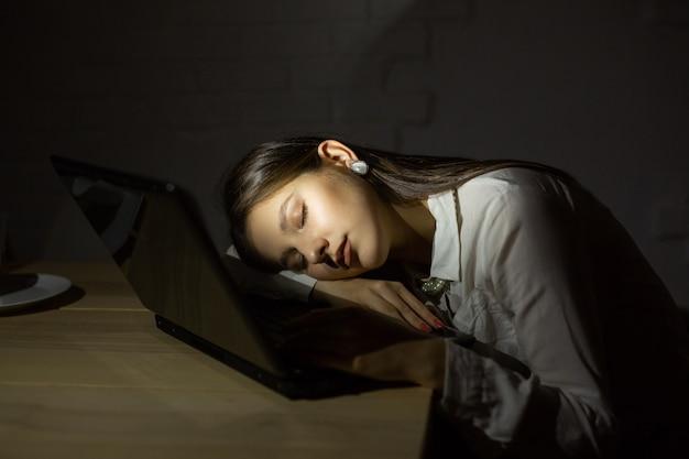 ノートパソコンの後ろで夜寝ている美しい若い女性