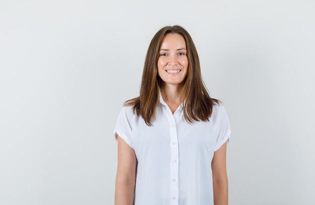 Bella giovane donna sorridente in camicetta bianca e guardando allegra