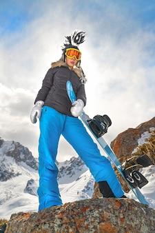산에 파란 스노우보드와 재미있는 모자를 쓴 아름다운 젊은 여성 스노보더 카메라를 봐