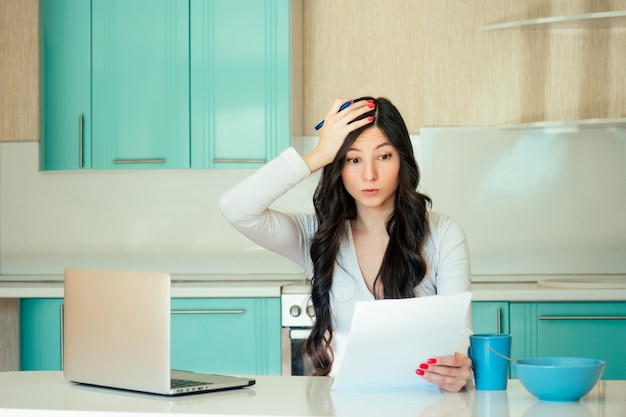 A beautiful young female student (freelancer) in a white dress and black hair works at home with a laptop and papers in a turquoise kitchen. the idea of solving the problem and deadline