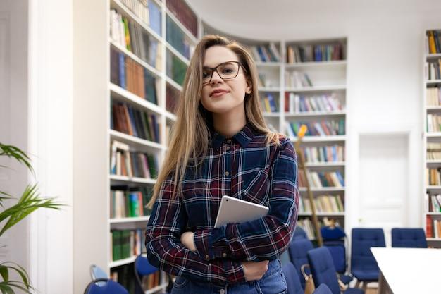 Красивая молодая студентка стоит в комнате библиотеки колледжа на фоне полок при книги держа таблетку в ее руках.