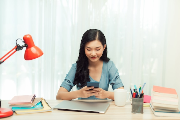 Beautiful young female student is using a smartphone and taking notes while sitting at desk