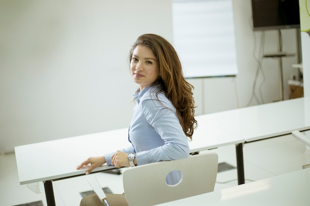 Beautiful young female student sitting on a chair and turning back