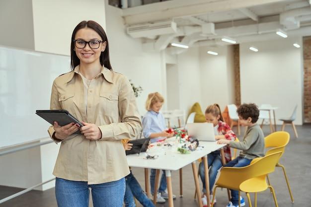 Красивая молодая учительница в очках улыбается и держит планшетный пк, позируя перед камерой