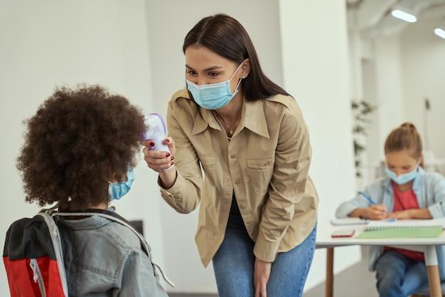 체온을 조금 측정하는 보호 마스크를 쓴 아름다운 젊은 여교사