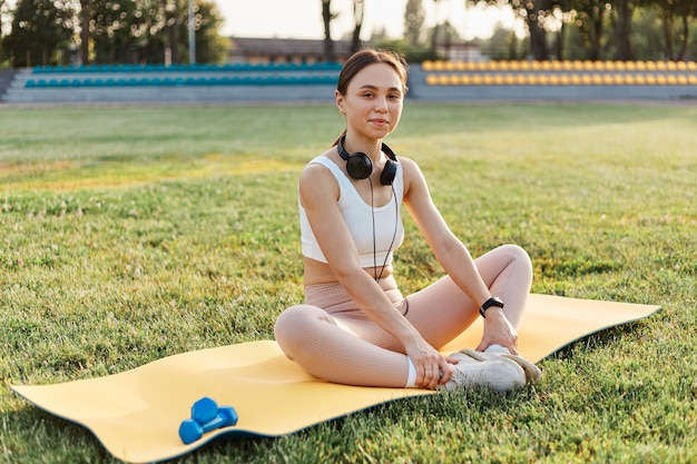 Beautiful young female wearing white top and beige leggins sitting on yellow karemat with headphones over neck
