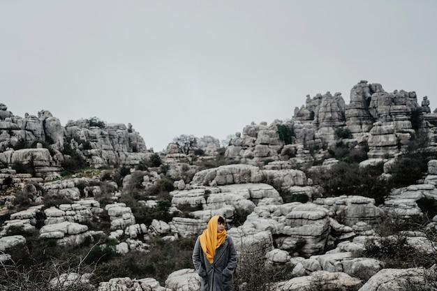 コートと高い岩の崖の近くに立っている黄色のスカーフと美しい若い女性