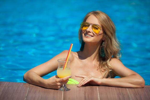 Красивая молодая женщина с напитком в бассейне