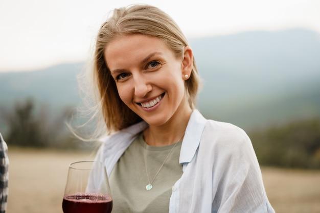 Красивая молодая женщина с бокалом красного вина в горах