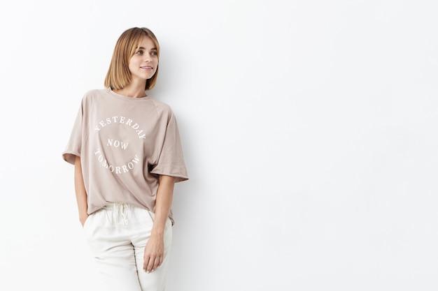 緩いシャツと白いズボンを身に着けて、ブーブヘアの美しい若い女性