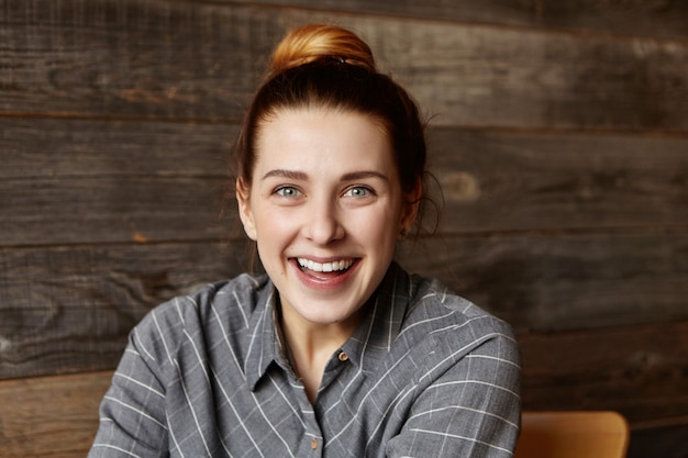 うれしそうな顔をして、陽気に笑って、いくつかの肯定的なニュースに満足して髪のパンと美しい若い女性