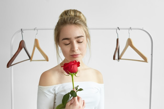 Beautiful young female with hair bun and naked shoulders posing with empty hangers, keeping eyes closed, enjoying sweet fresh aroma coming form red rose in her hands