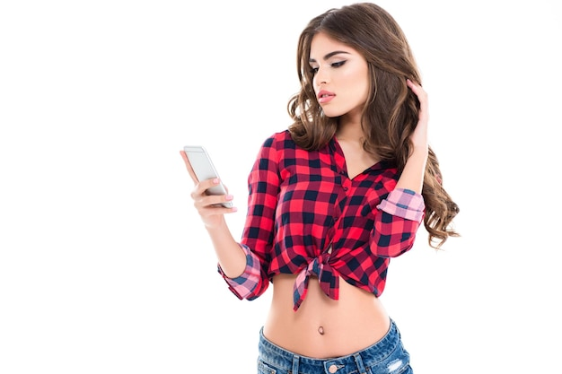 Beautiful young female with long curly hair in checkered shirt using mobile phone over white wall