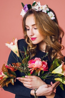 Beautiful young female with long wavy blonde  hair in wreath of spring flowers  posing with flower bouquet over   pink  background.