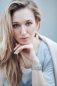 長いウェーブのかかった髪とイヤリングの宝石で美しい若い女性。女性の自然の美しさ、優しくメイクや化粧品