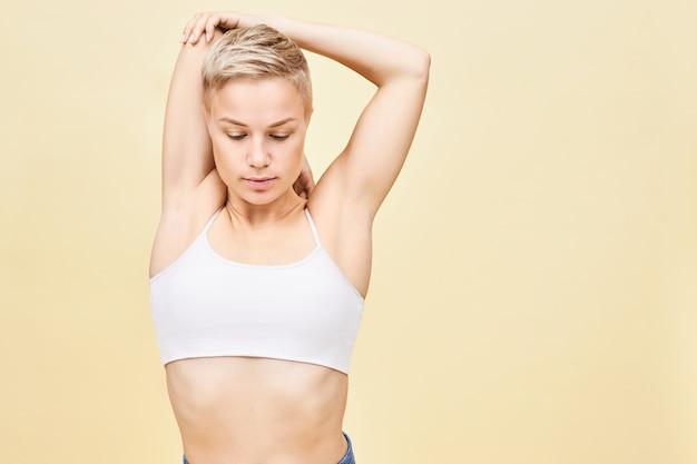 Bella giovane donna con l'acconciatura da folletto e il corpo in forma allungando le braccia, facendo esercizio per migliorare la mobilità dell'articolazione della spalla. bella ragazza che indossa top bianco a praticare yoga