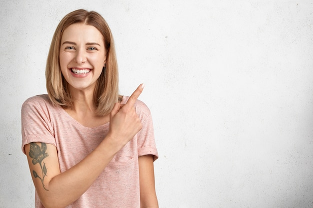 肯定的な表情の美しい若い女性はタトゥーを入れ、気持ちよく笑顔を見せ、宣伝文や広告コンテンツの空白のコピースペースを示しています。