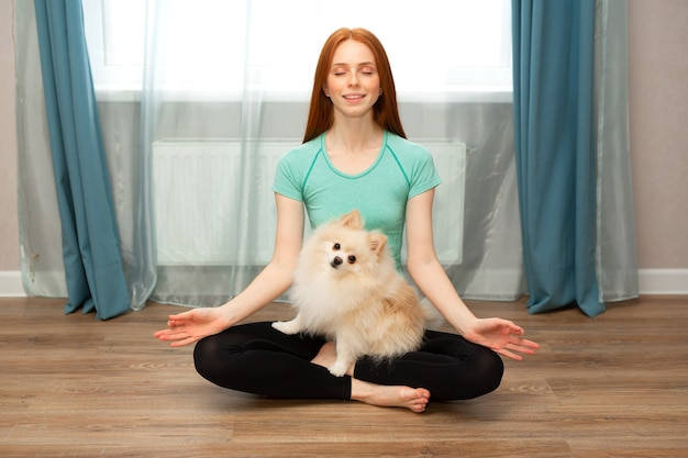 Beautiful young female with red hair goes in for sports at home with a dog