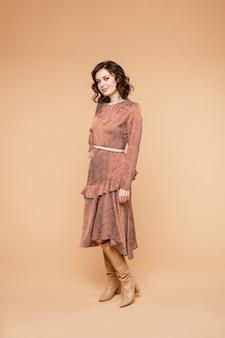 短い黒髪、長いオレンジ色のドレスのきれいな顔、黄土色の長いブーツの笑顔を持つ美しい若い女性