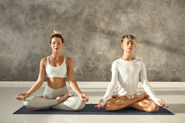 Beautiful young fit female and muscular male practicing meditation together in lotus pose, sitting on one mat at gym with grey copyspace wall, keeping eyes closed and holding hands in mudra