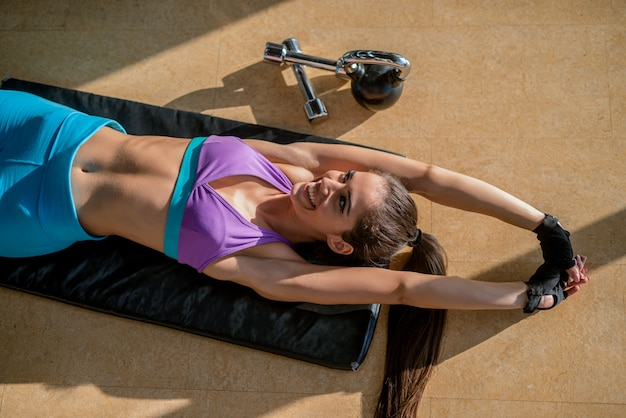 Beautiful young fit girl lying down on gym floor and stretch her muscles after hard training.
