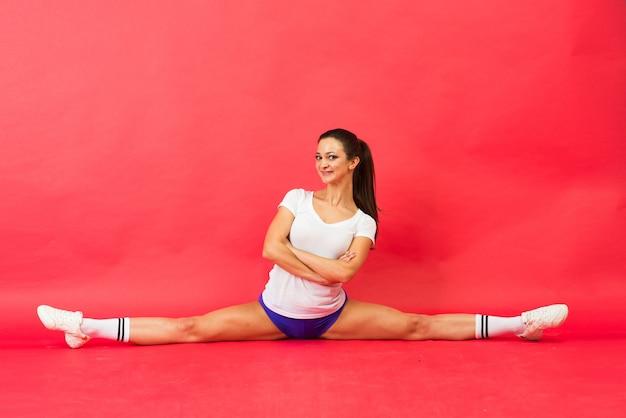 Красивая молодая женщина подходит гимнастка в спортивной одежде, элемент исполнительского искусства гимнастики
