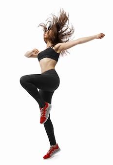 美しい若いフィットフライング彼女の長い髪で踊るモダンダンサーの女性