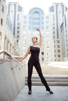 Красивая молодая подтянутая стройная балерина позирует возле перил