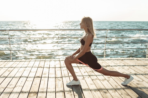 Beautiful young fit woman doing morning exercise with fitness rubber bands at beach.