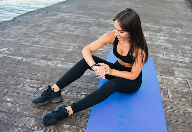 해변에서 매트에 앉아있는 동안 아름다운 젊은 맞는 여자가 스마트 팔찌를 즐긴다