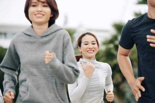 Красивая молодая подтянутая женщина улыбается в камеру во время пробежки на открытом воздухе со своими друзьями