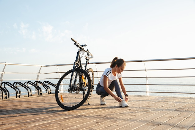 Beautiful young fitness girl outdoors with a bicycle, sea landscape, tying her shoelace