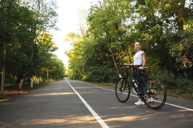 Красивая молодая фитнес-девушка гуляет с велосипедом по парковой дороге