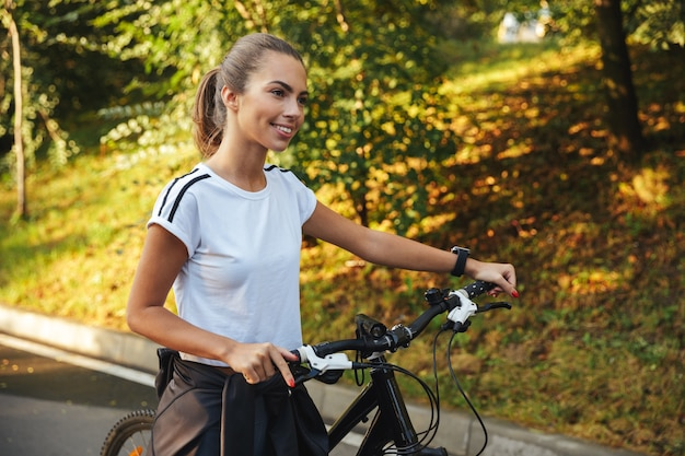 Beautiful young fitness girl walking with bicycle at the park road