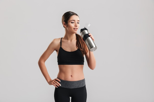 Beautiful young fitness instructor wearing tracksuit looking aside and drinking fresh still water from metal bottle, isolated over gray wall