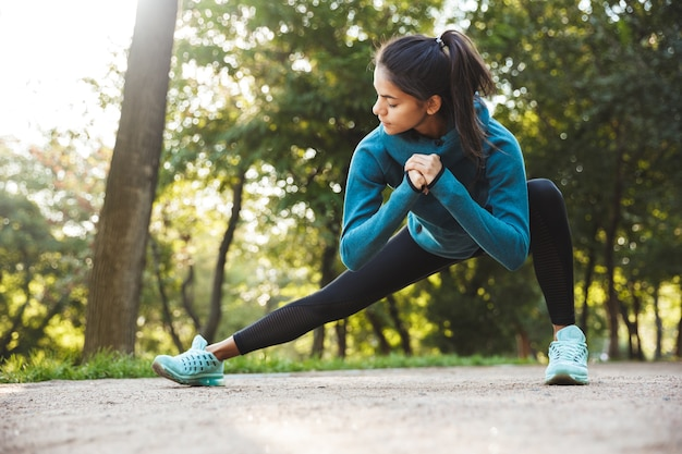 Beautiful young fitness woman doing morning exercising at the park