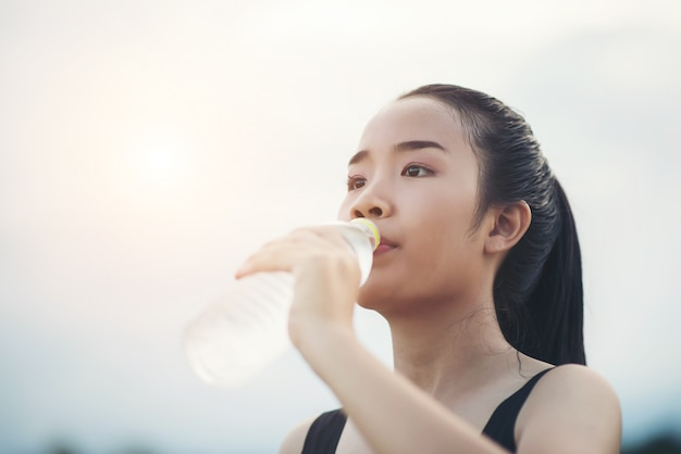 Beautiful young fitness woman drinking water after running exercise