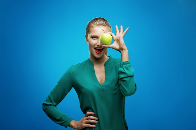 Beautiful young fitness woman happy smile hold green apple. healthy lifestyle photo isolated on blue wall