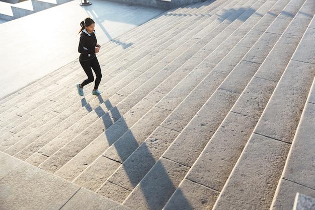 Красивая молодая женщина фитнеса носить спортивную одежду, бег на лестнице на открытом воздухе