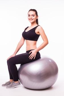 Красивая молодая женщина фитнеса с гимнастическим мячом упражнения, изолированные на белом фоне