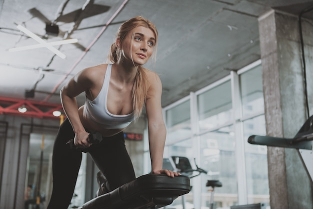 Beautiful young fitness woman working out at the gym