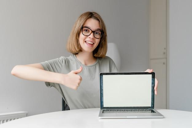 Красивая молодая женщина-фрилансер, показывая экран макета портативного компьютера и большой палец вверх сидя дома. внештатная работа, концепция онлайн-образования