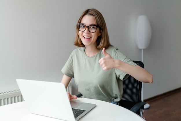 Beautiful young freelancer woman using laptop computer sitting at home show thumb up. freelance work, business people concept