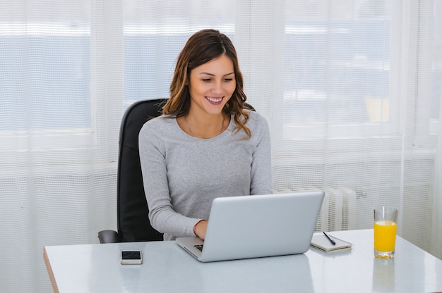 Beautiful young freelancer woman using laptop computer
