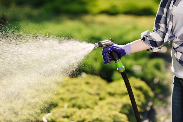 뜨거운 여름 날에 정원을 급수하는 아름 다운 젊은 정원사 여자.