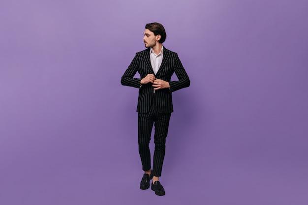 세련된 양복, 흰색 셔츠, 검은색 신발을 신고 재킷을 곧게 펴고 옆을 바라보는 아름다운 젊은 신사