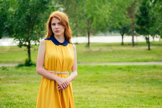 Beautiful young ginger redhead irish woman in a yellow dress stylish in the summer park . concept of freshness and femininity
