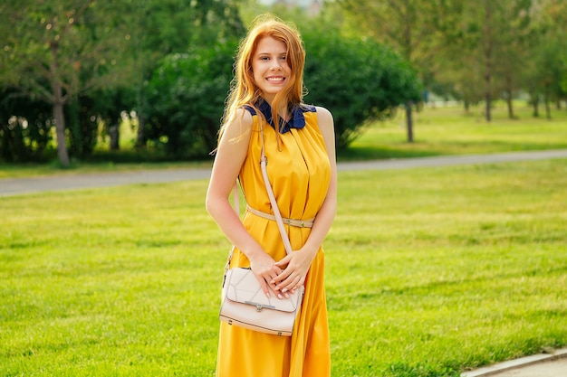 Beautiful young ginger redhead scottish woman in a yellow dress with stylish bag in the summer park