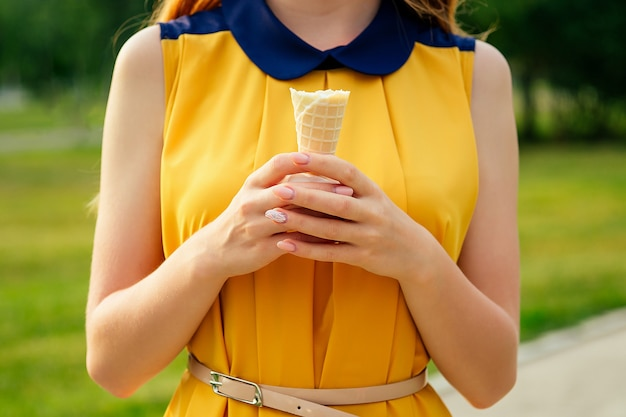 And beautiful young ginger redhead woman in a yellow dress eating vanilla ice cream in a waffle cone in the summer park