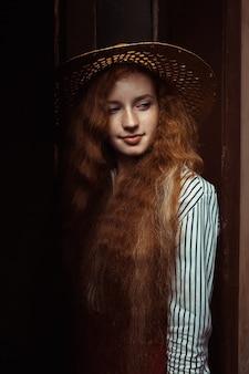 古い通路でポーズをとる麦わら帽子のそばかすを持つ美しい若い生姜の女性